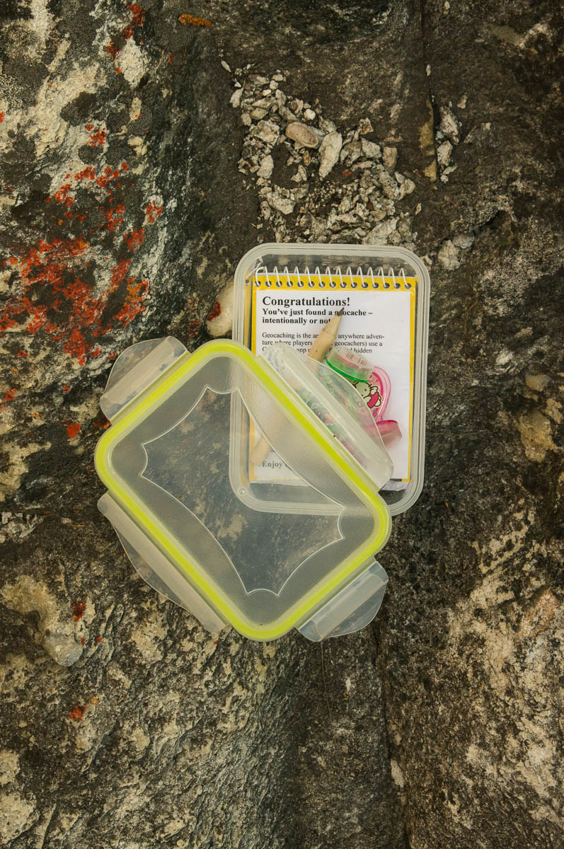 Geocache box with notebook and treasure